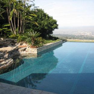 Diseño de piscina alargada, marinera, de tamaño medio, a medida, en patio trasero, con adoquines de piedra natural
