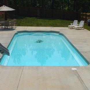 Foto de piscina con tobogán alargada, clásica, grande, rectangular, en patio trasero, con losas de hormigón