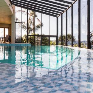 Modelo de piscina infinita, contemporánea, grande, interior y a medida, con privacidad y suelo de baldosas