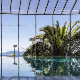 Ejemplo de piscina infinita, contemporánea, grande, interior y a medida, con privacidad y suelo de baldosas