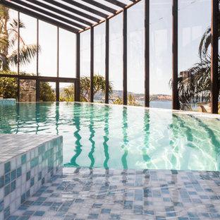 Inspiration pour une grand piscine intérieure à débordement design sur mesure avec des solutions pour vis-à-vis et du carrelage.