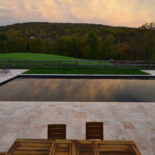 Photo of a large arts and crafts backyard rectangular lap pool in DC Metro with natural stone pavers.