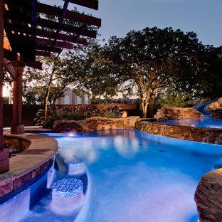 Idée de décoration pour une très grand piscine naturelle et arrière ethnique sur mesure avec un toboggan et des pavés en pierre naturelle.