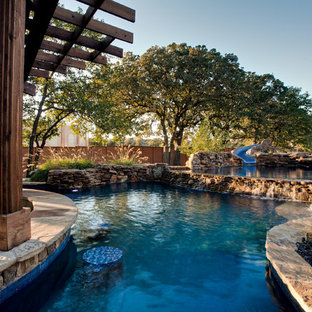 Imagen de piscina con tobogán natural, tropical, extra grande, a medida, en patio trasero, con adoquines de piedra natural