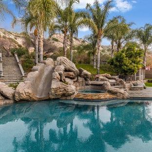 Idée de décoration pour une grand piscine arrière ethnique sur mesure avec un toboggan et des pavés en béton.