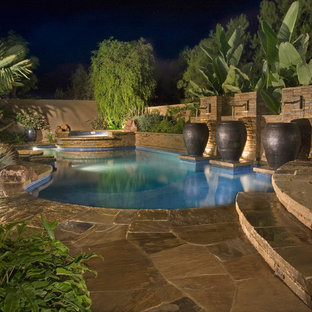This is an example of a mediterranean backyard custom-shaped pool in Orange County with a water feature.
