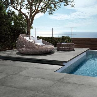 Diseño de piscina alargada, minimalista, rectangular, en patio trasero, con suelo de baldosas