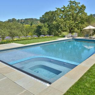 Modelo de piscinas y jacuzzis alargados, de estilo americano, grandes, rectangulares, en patio trasero, con adoquines de hormigón