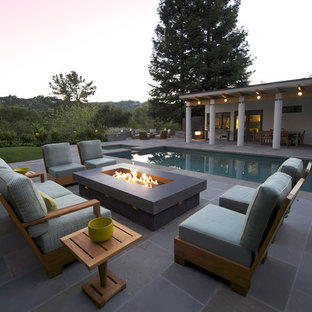 This is an example of a contemporary back rectangular lengths swimming pool in San Francisco with natural stone paving.