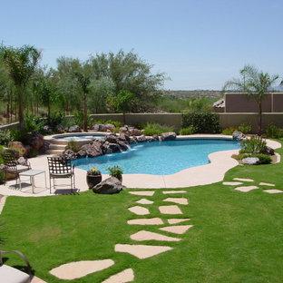 Foto de piscina con fuente contemporánea, de tamaño medio, tipo riñón, en patio trasero, con losas de hormigón