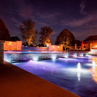 Ejemplo de piscina con fuente infinita, clásica, grande, rectangular, en patio trasero, con adoquines de piedra natural