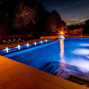 Foto de piscina con fuente infinita, tradicional, grande, rectangular, en patio trasero, con adoquines de piedra natural