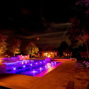 Foto på en stor vintage infinitypool på baksidan av huset, med en fontän och naturstensplattor