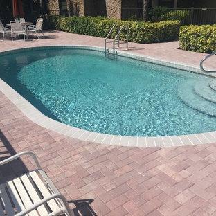 Diseño de piscina alargada, mediterránea, de tamaño medio, redondeada, en patio trasero, con adoquines de ladrillo