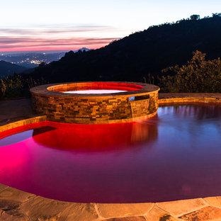 Aménagement d'une grand piscine naturelle et arrière contemporaine sur mesure avec un bain bouillonnant et des pavés en pierre naturelle.