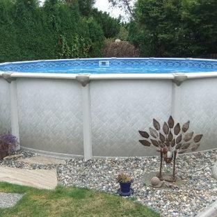 Ejemplo de piscina elevada, redondeada, en patio trasero, con gravilla