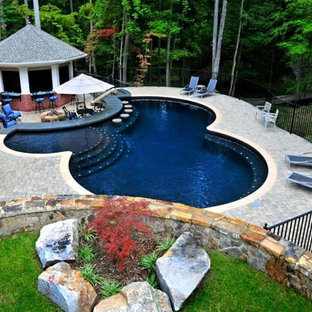 Mid-sized traditional backyard round lap pool in New York with a pool house and brick pavers.