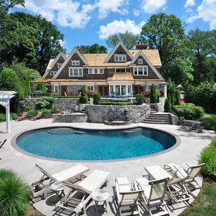 Foto de piscina alargada, clásica, extra grande, redondeada, en patio trasero, con adoquines de hormigón