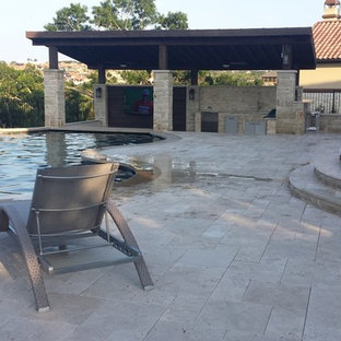 Photo of a large traditional backyard custom-shaped pool in Austin with concrete pavers.