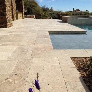 Foto de piscinas y jacuzzis de estilo americano, grandes, en forma de L, en patio trasero, con adoquines de piedra natural