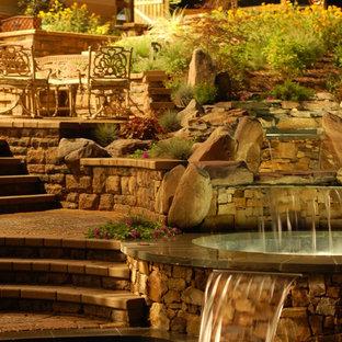 Foto de piscina con fuente natural, clásica renovada, de tamaño medio, a medida, en patio trasero, con adoquines de ladrillo