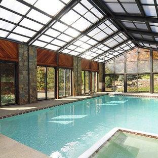 Foto de casa de la piscina y piscina alargada, tradicional, grande, interior y rectangular, con losas de hormigón