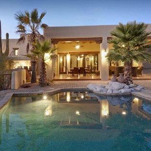 Foto de piscina alargada, de estilo americano, grande, a medida, en patio trasero, con adoquines de piedra natural