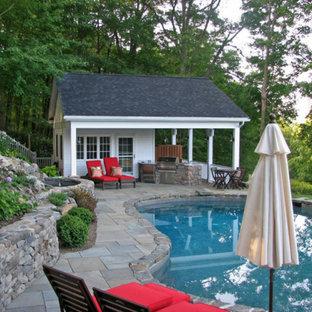 Ispirazione per una piscina naturale costiera personalizzata di medie dimensioni e dietro casa con una dépendance a bordo piscina e pavimentazioni in pietra naturale