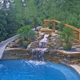 Ispirazione per una piscina design personalizzata di medie dimensioni e dietro casa con un acquascivolo e pavimentazioni in pietra naturale