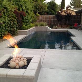 Diseño de piscina con fuente alargada, tradicional, grande, rectangular, en patio trasero, con losas de hormigón