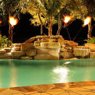 Modelo de piscina con fuente alargada, tradicional, de tamaño medio, a medida, en patio trasero, con adoquines de piedra natural