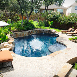 Inspiration for a small traditional backyard custom-shaped lap pool in Austin with a water feature and natural stone pavers.
