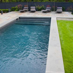Immagine di una piscina monocorsia classica rettangolare di medie dimensioni e dietro casa con graniglia di granito