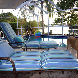 Florida - Outdoor Living - Cushions - These two-break chaise cushions in Sunbrella Dolce Oasis (56001-0000) brighten the patio and accent the pool tiles colors. The lumbar pillows feature both Aruba (5416-0000) and Spectrum Sailor (48021-0000) fabrics by Sunbrella with Dolce Oasis cording. Cushion Source's Chaise cushions are available in 1, 2, and 3 breaks and with hundreds of fabric options and ANY size. (Customer Photo)