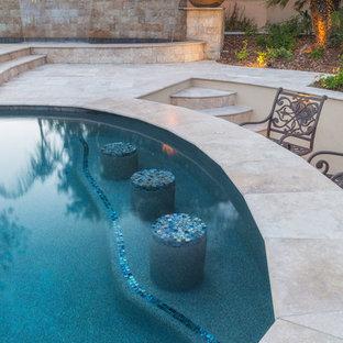 Esempio di una grande piscina mediterranea personalizzata dietro casa con piastrelle e fontane