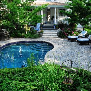 Diseño de piscina con fuente alargada, de estilo americano, grande, tipo riñón, en patio trasero, con adoquines de piedra natural