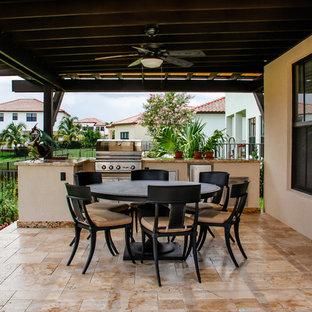 Small minimalist backyard stone and custom-shaped aboveground hot tub photo in Miami