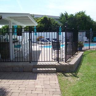 """Esempio di una grande piscina costiera a """"C"""" dietro casa con pavimentazioni in cemento"""