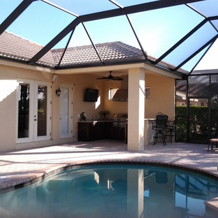 Inspiration for a mid-sized tropical backyard concrete paver and custom-shaped pool remodel in Miami