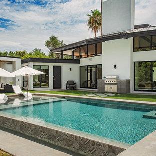 Foto di una piscina minimal rettangolare di medie dimensioni e dietro casa