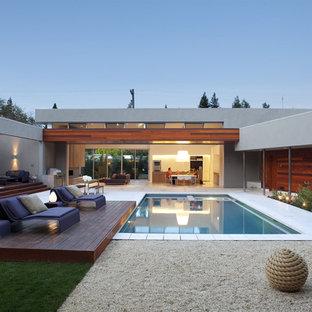 На фото: бассейн на внутреннем дворе в стиле модернизм с настилом с