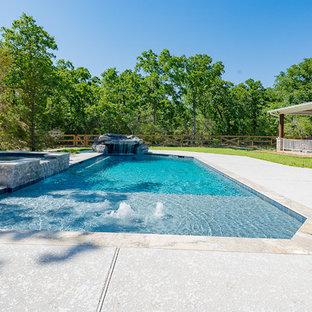 Modelo de piscinas y jacuzzis modernos, grandes, a medida, en patio trasero, con losas de hormigón