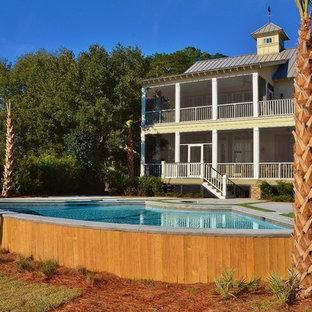 Immagine di una piscina fuori terra stile marinaro personalizzata di medie dimensioni e dietro casa con fontane e lastre di cemento