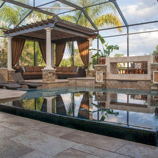Photo of a small transitional custom-shaped infinity pool in Tampa with natural stone pavers.