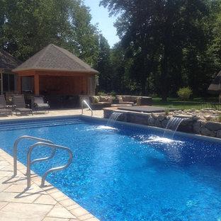 Ejemplo de piscina con fuente tradicional, grande, rectangular y interior, con adoquines de ladrillo