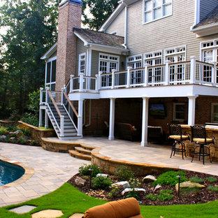 Diseño de piscinas y jacuzzis alargados, clásicos, de tamaño medio, tipo riñón, en patio trasero, con adoquines de hormigón