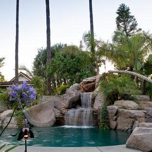 Esempio di una piscina naturale tropicale con un acquascivolo