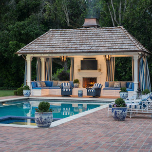 Idéer för att renovera en stor vintage rektangulär träningspool på baksidan av huset, med poolhus och marksten i tegel