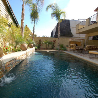 This is an example of a large mediterranean backyard rectangular lap pool in San Diego with a water feature and gravel.