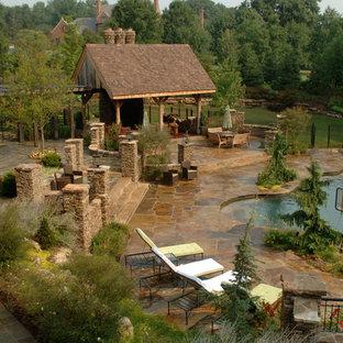 Inspiration pour une grand piscine naturelle et arrière craftsman sur mesure avec un toboggan et des pavés en pierre naturelle.